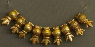 Περιδέραιο με χρυσά περίαπτα ρόδια, από τον Τάφο III του Ταφικού Κύκλου Α των Μυκηνών (16ος αι. π.Χ.). Αθήνα, Εθνικό Αρχαιολογικό Μουσείο.jpg